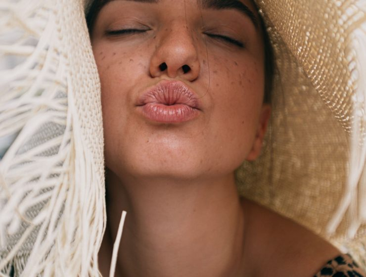 woman pouting towards camera with eyes closed and wearing a straw beach hat