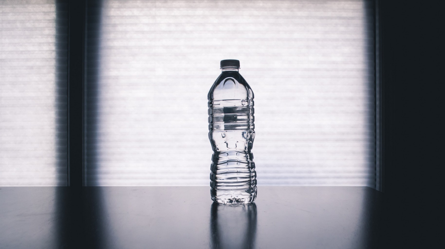 a full bottle of water, with no label, on a black table with a shadowed white background.