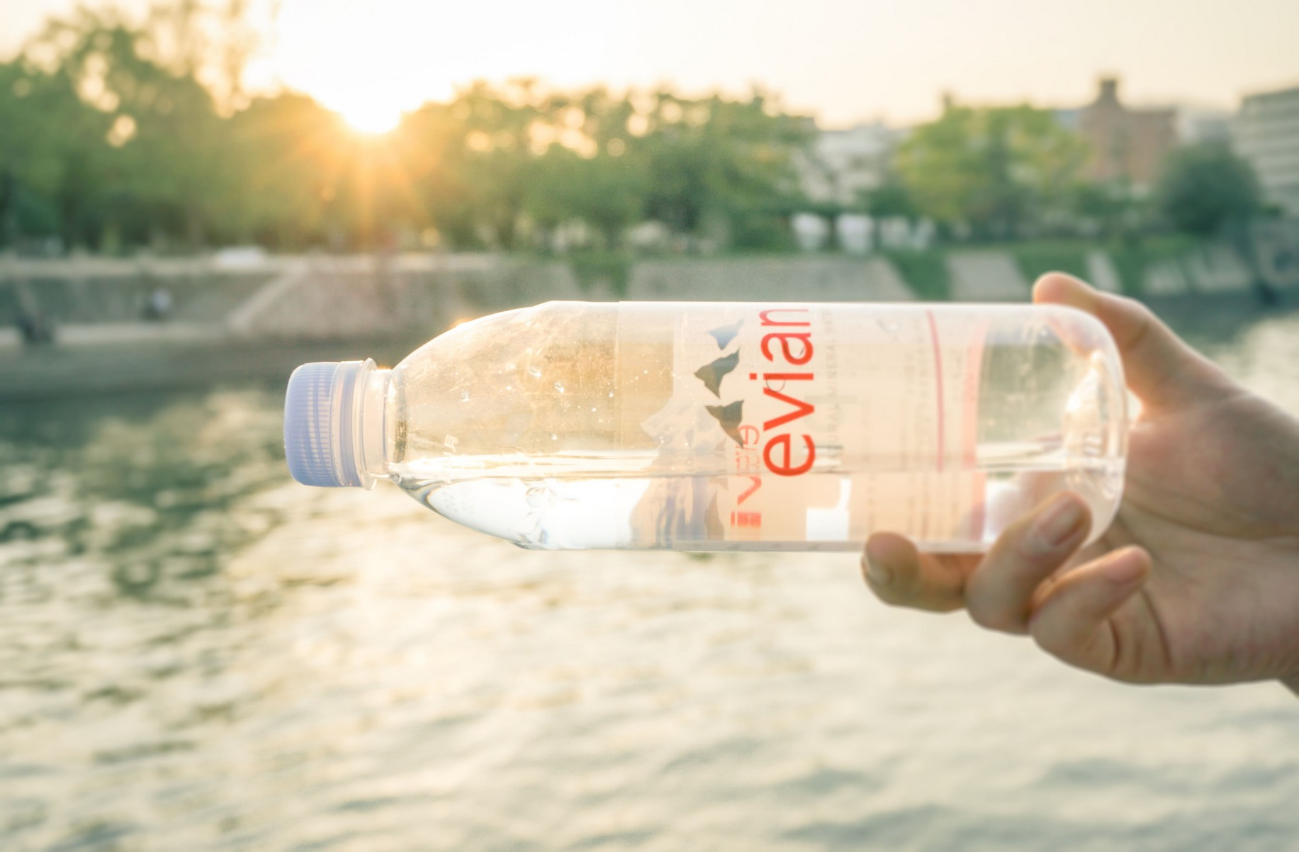 a hand holding a bottle of Evian water horizontally over the sea.