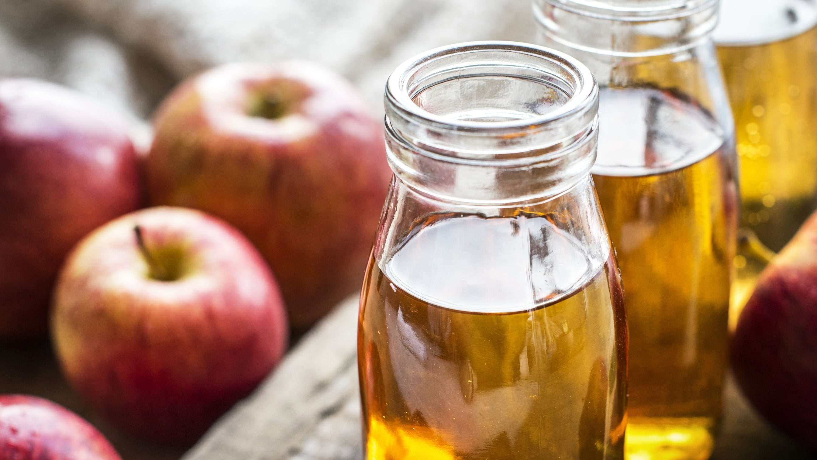 acne scars can be improved with glass jars of apple cider vinegar, next to an array of apples.