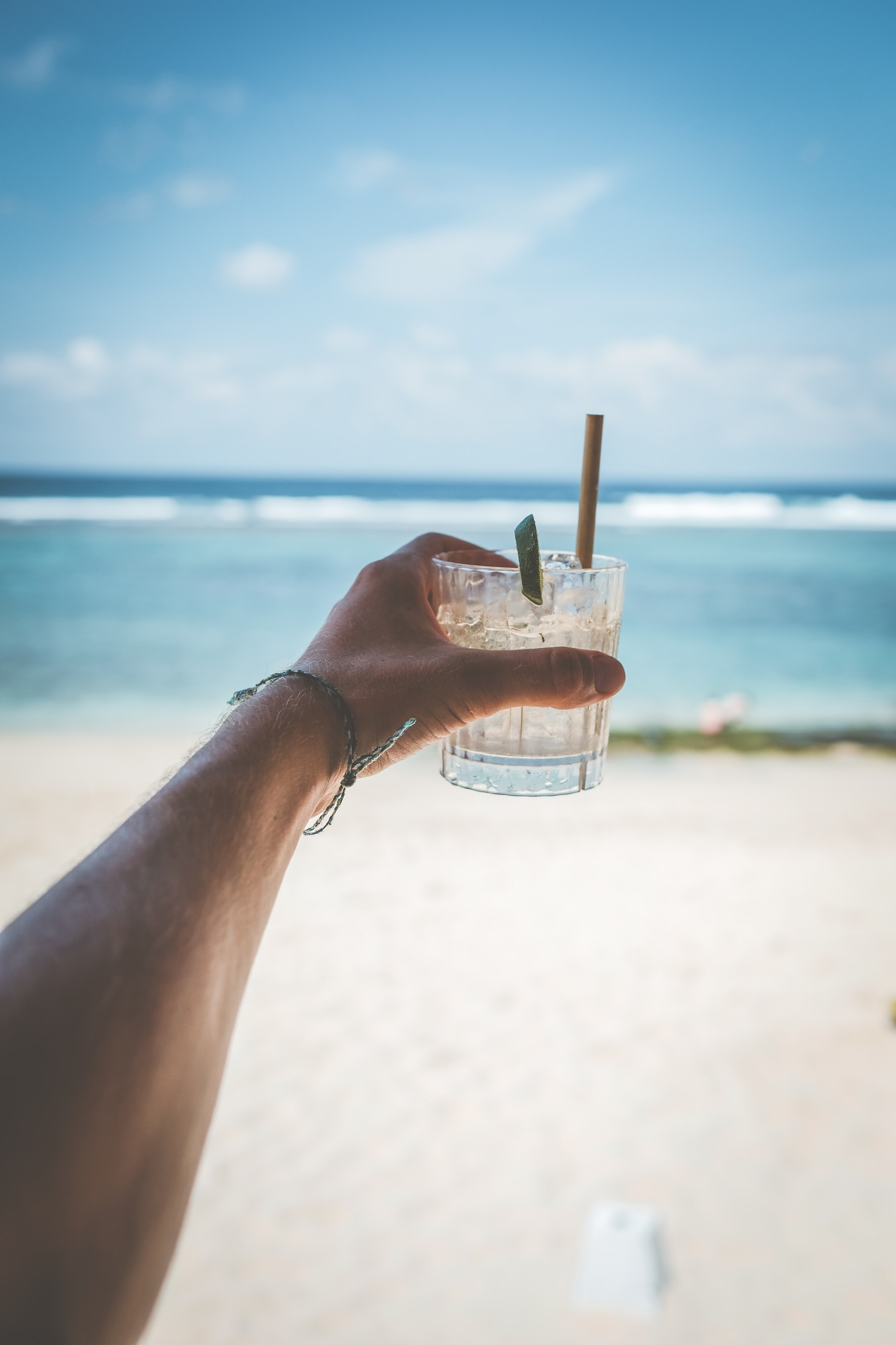 an arm stretched out towards the sea, whilst on the beach, holding a short glass of ice cold water with flavour sticks/straws.