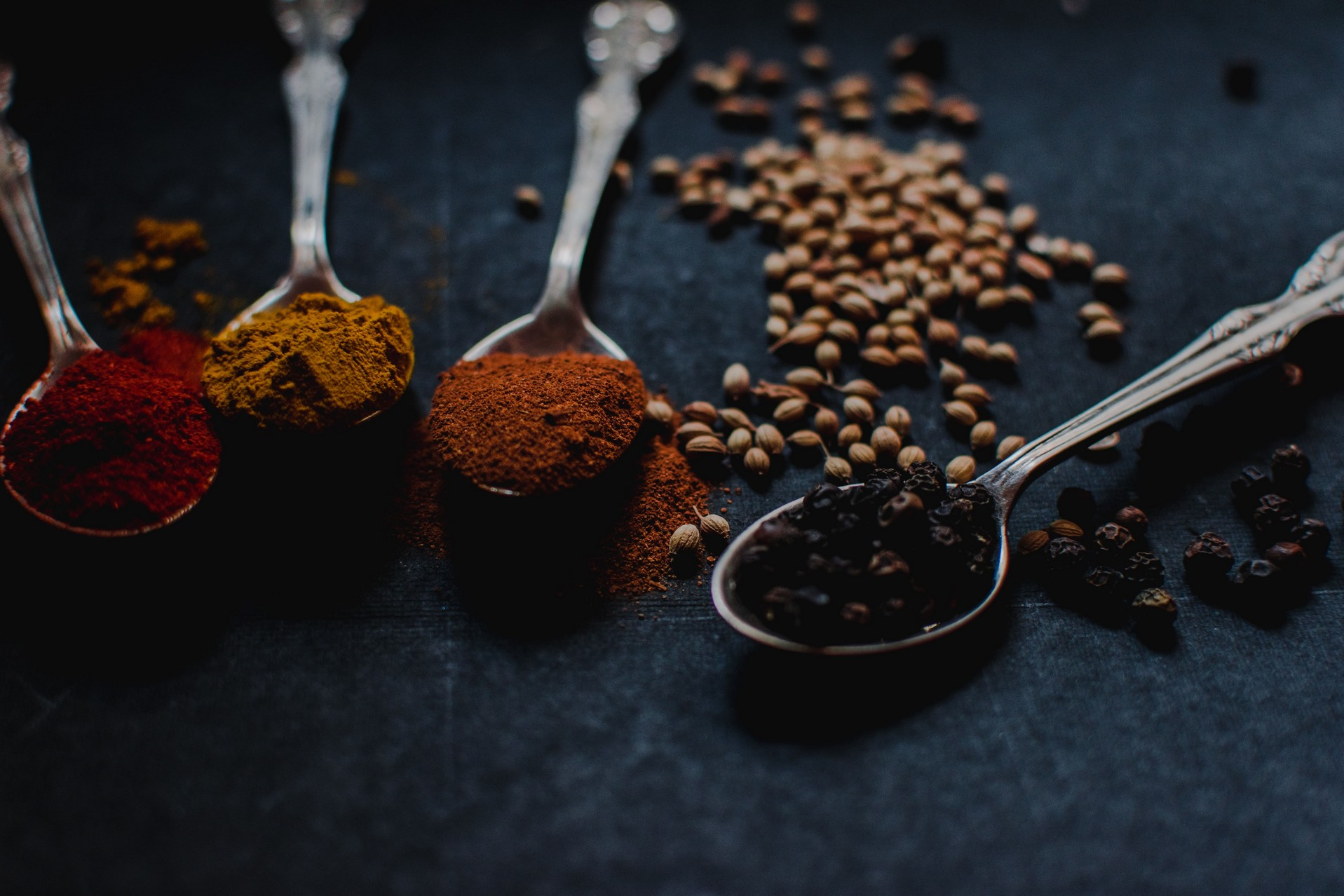 array of spices overflowing on silver spoons on a black background