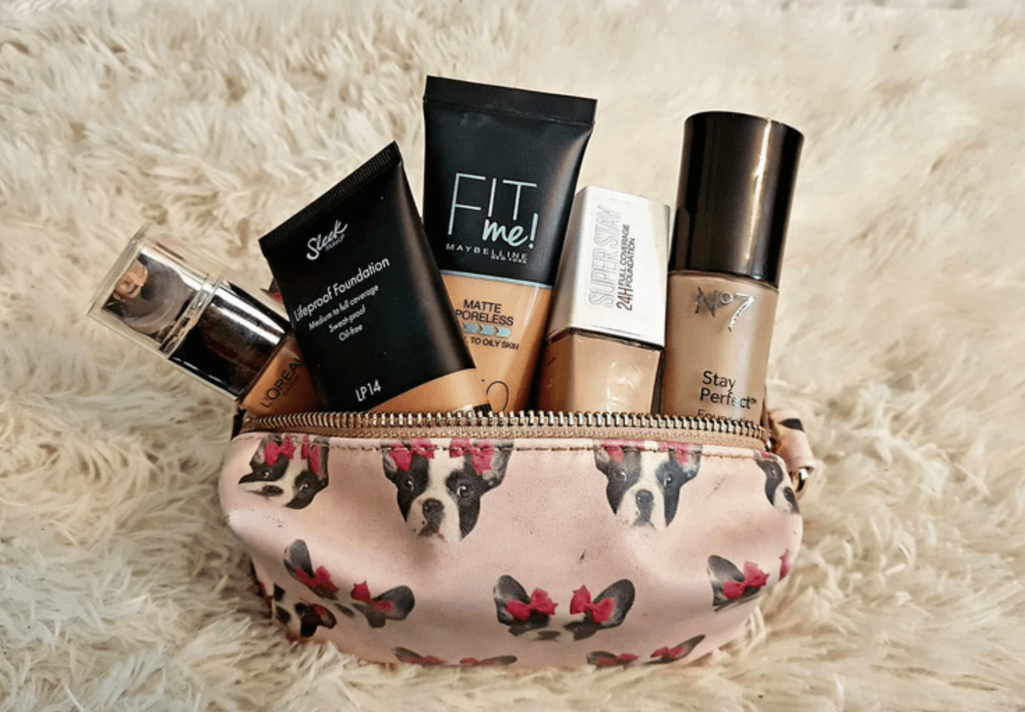 Liquid foundations pappearing out of an opened, pink makeup bag