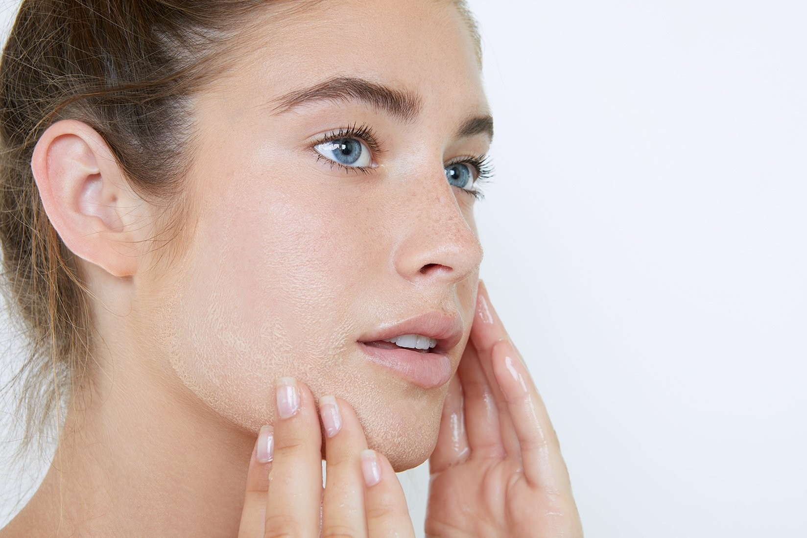 woman cleaning her face whilst touching her face lightly with her finger tips.