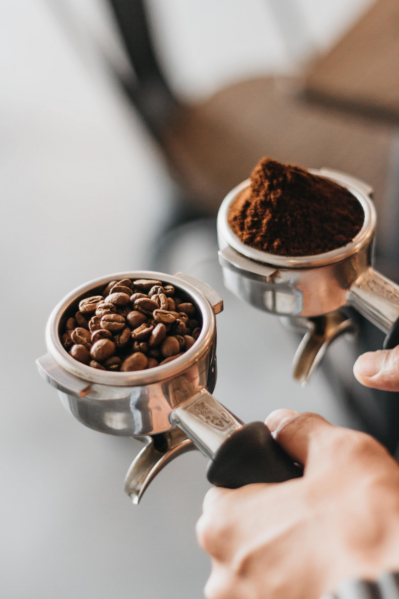 Two portafilters with black handles, being held, one with coffee beans and the other with grounded coffee beans.