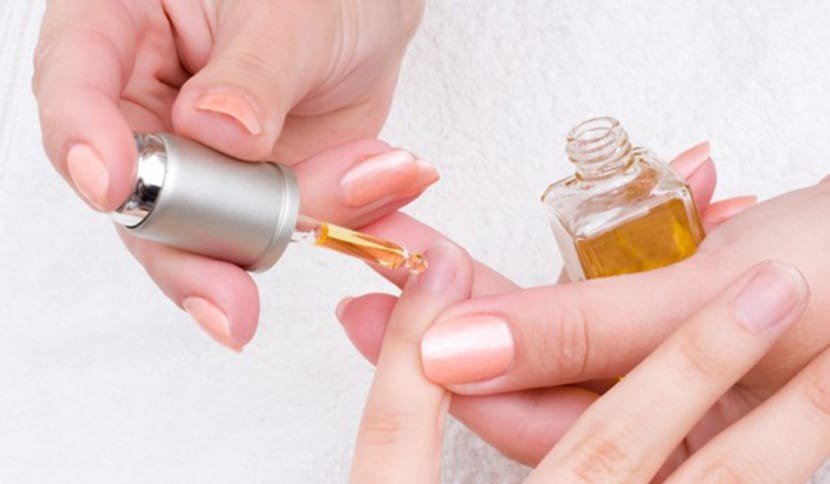 manicure prepping with two hands, one applying cuticle oil to the other hands nails.