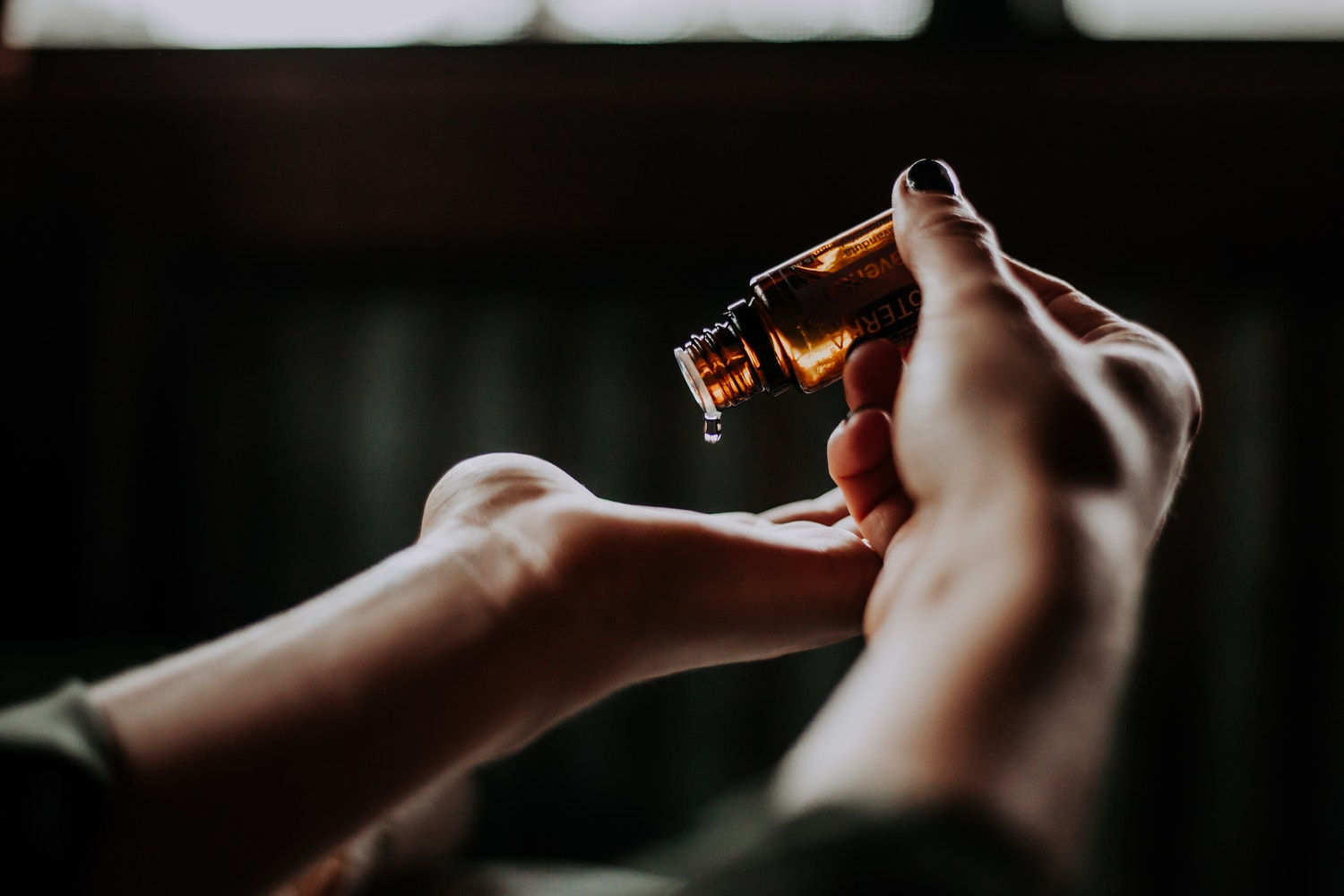 two hands pictured with one pouring a small bottle of essential oils into the other.