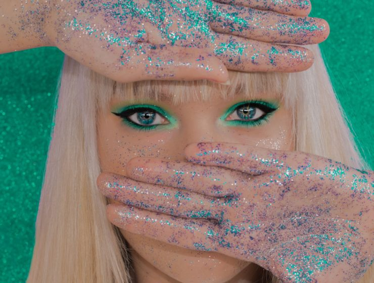 lady with blonde hair covered the top and bottom of her face with her hands, her palms exposed covered in blue/aqua glitter whilst she has green glittery eyeliner on.
