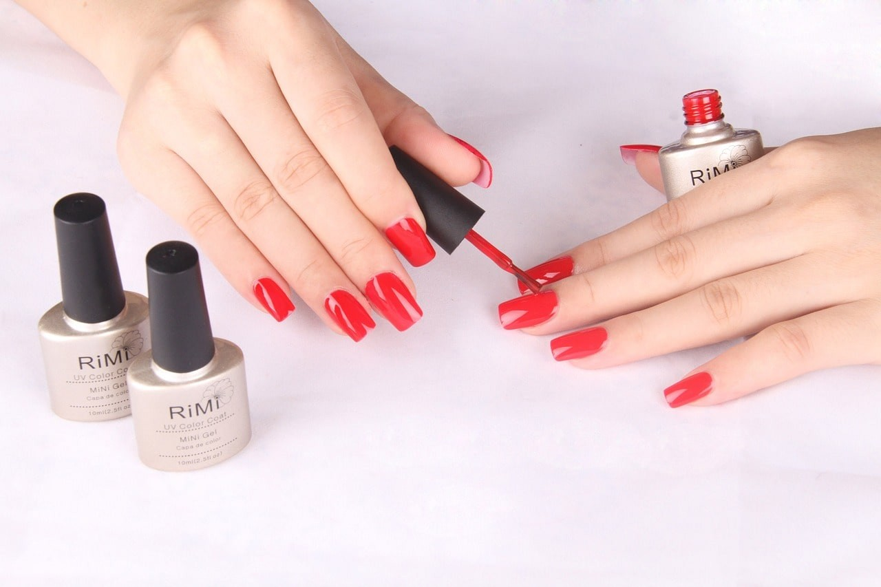A complete manicure. A lady applying red nail polish to her hands with two other polishes beside her on a light purple background