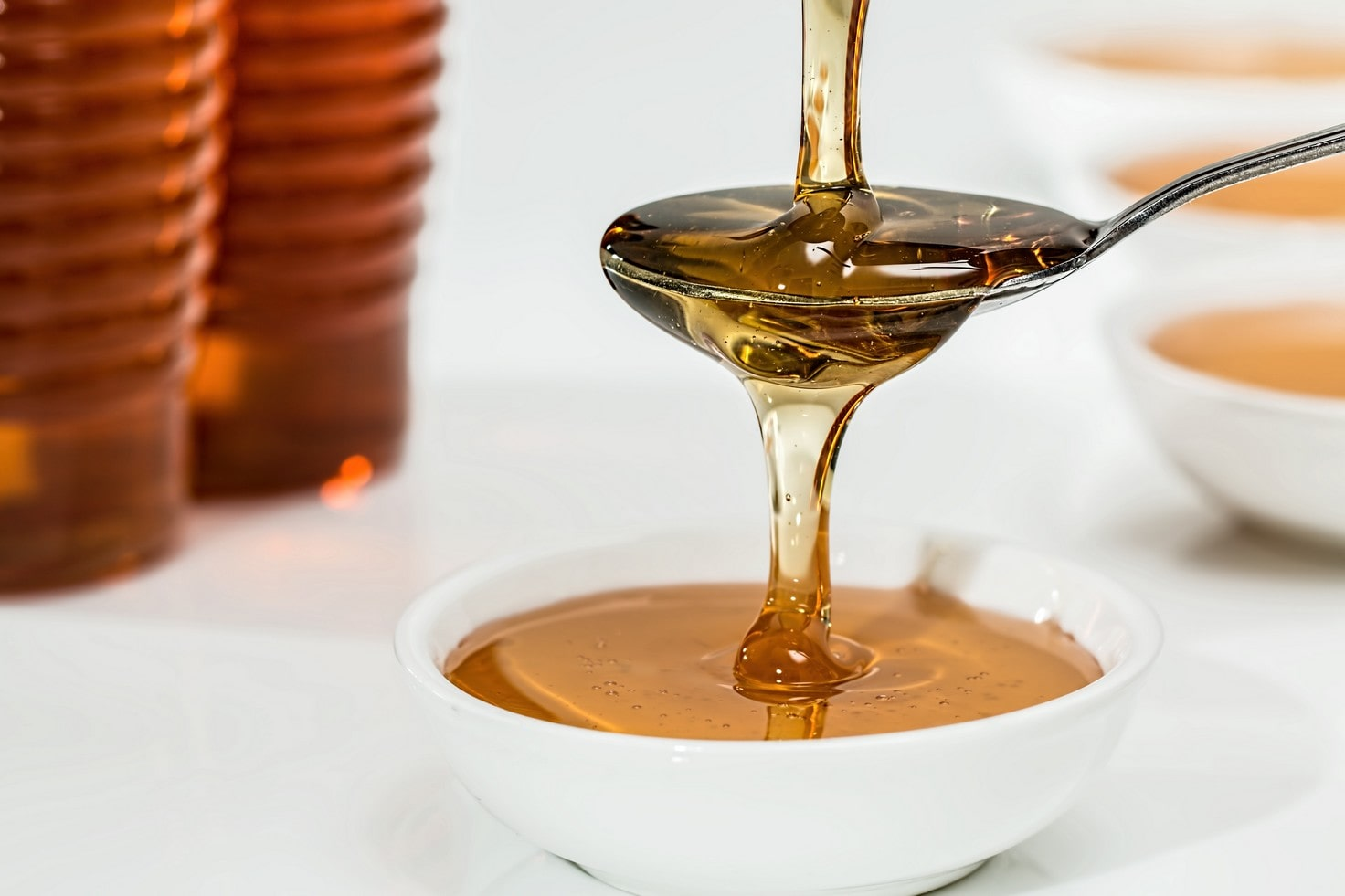acne scars can improve with raw honey, pictured being poured onto a spoon and overflowing into a white bowl below.
