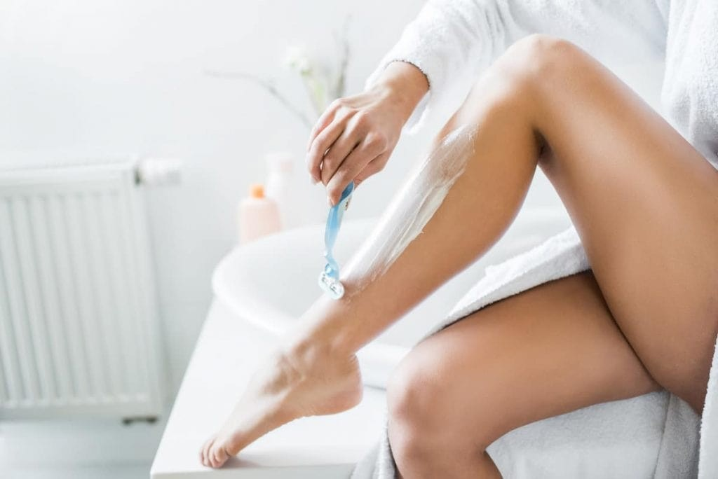 lady shaving her leg with a white bath sink in the background
