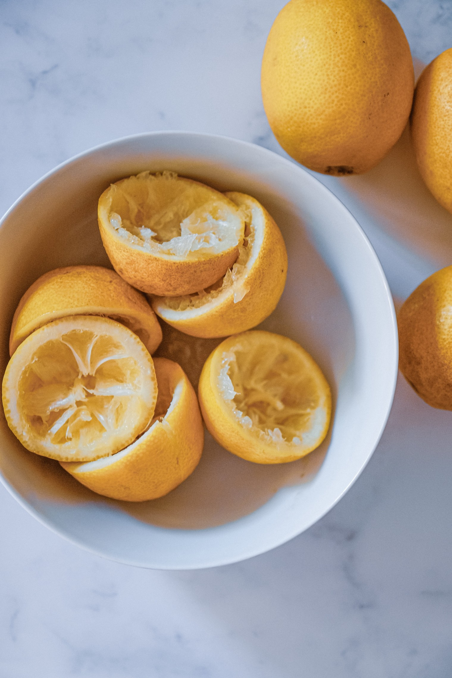 used lemons in a white bowl next to fresh whole lemons on a white background