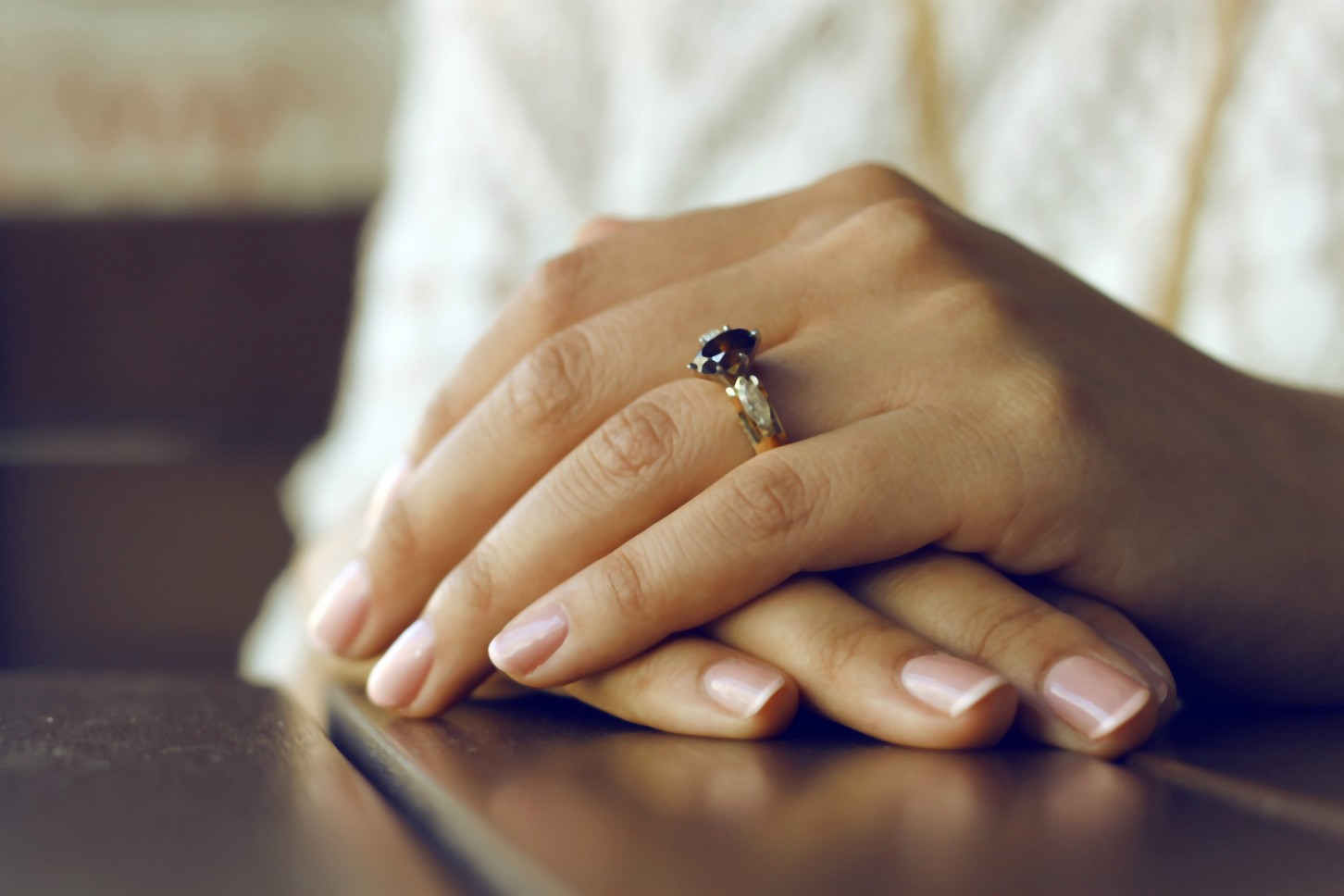 two hands folded over one another, with neatly manicured nails.