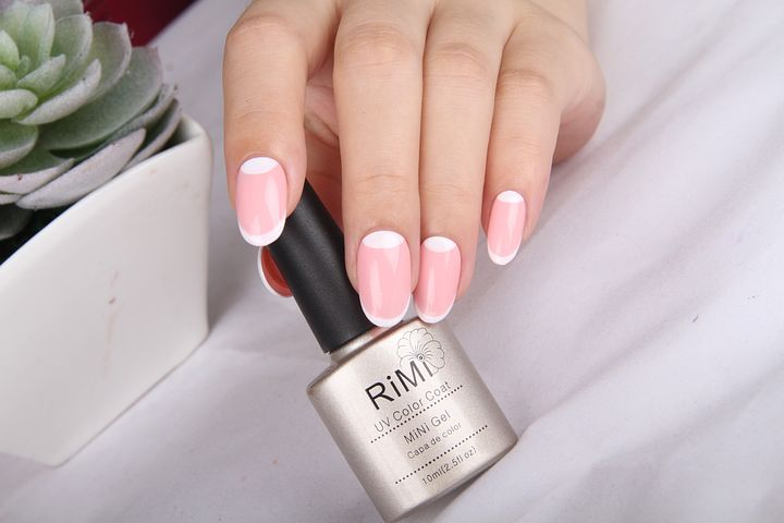 A complete manicure, a lady's hands with pink and white polish holding a bottle of nail polish with a plant near her hand.