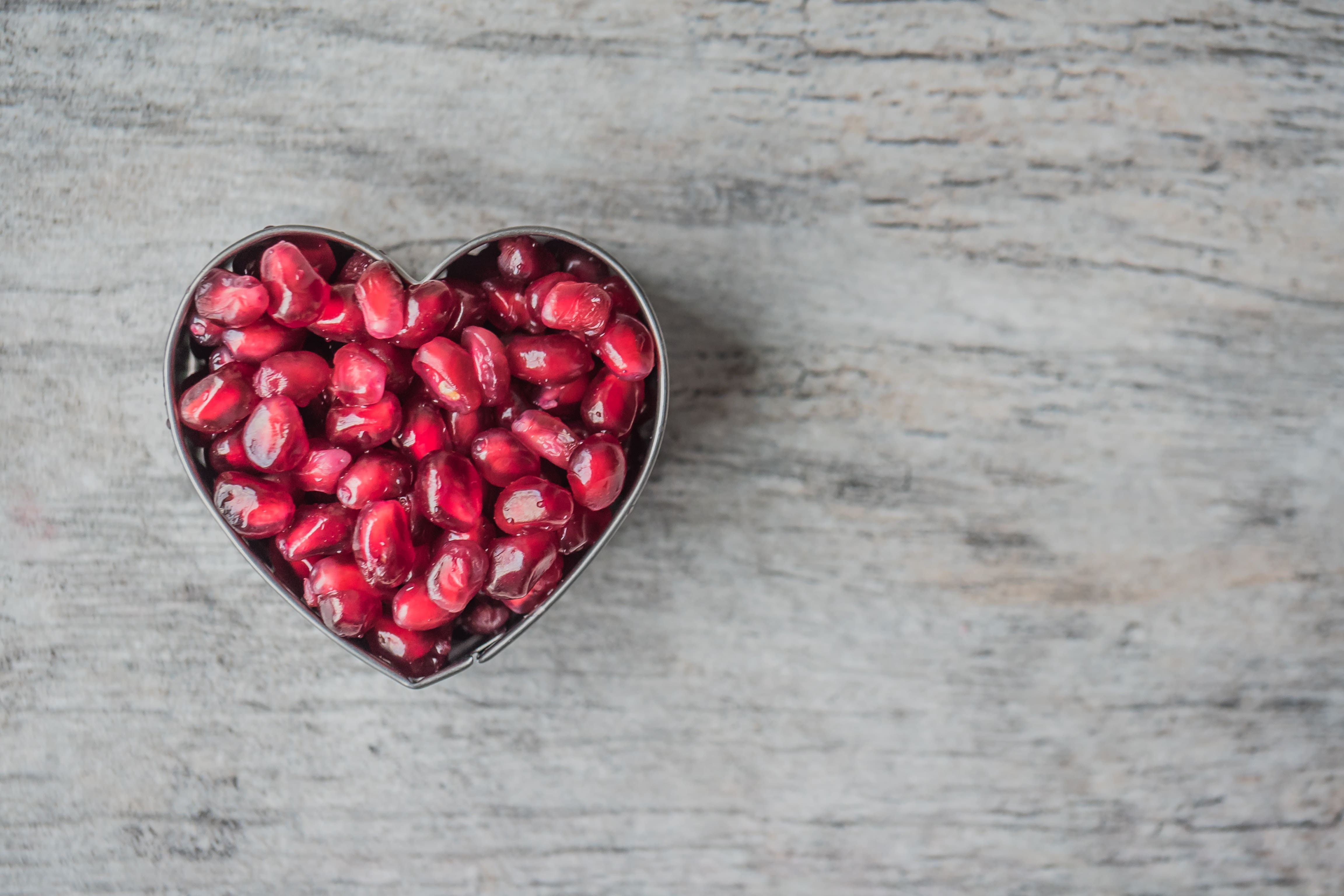 Pomegranate seeds within a heart-shaped-cake-cutter on a grey wooden background