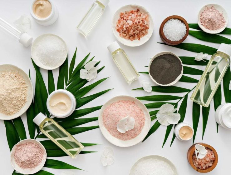 An array of natural ingredients, such as Chia seeds and sea salt, all laid upon a white background and two giant green leaves.