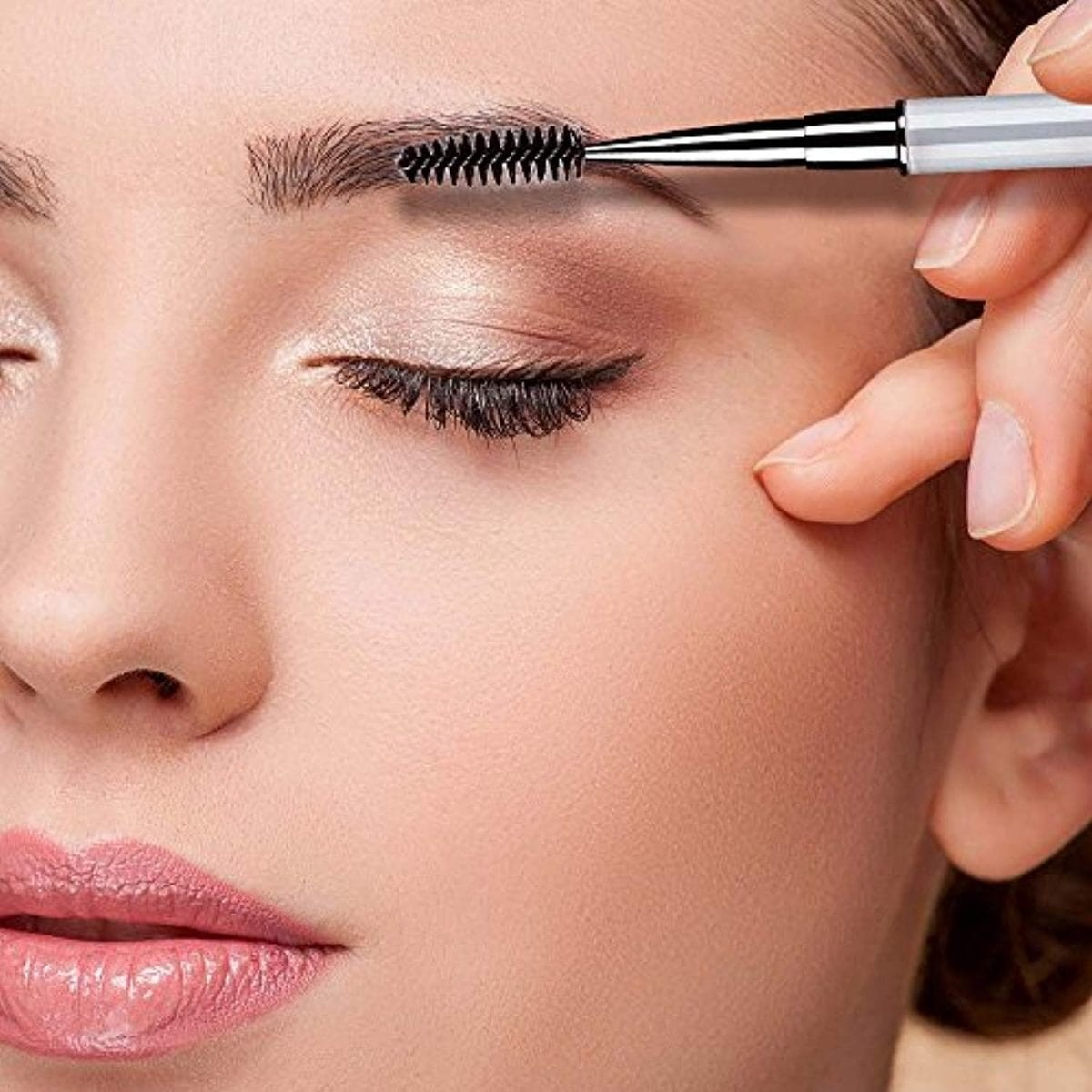 close up of woman's face, eyes closed and using a spoolie brush on her Eyebrows.