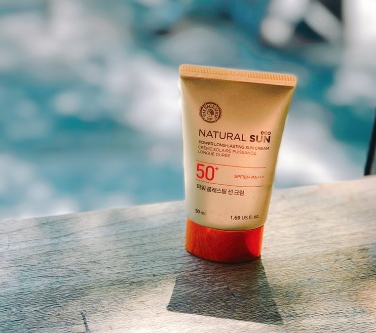A tube of sunscreen by a swimming pool. Sunscreen is essential in helping to prevent sunburn.