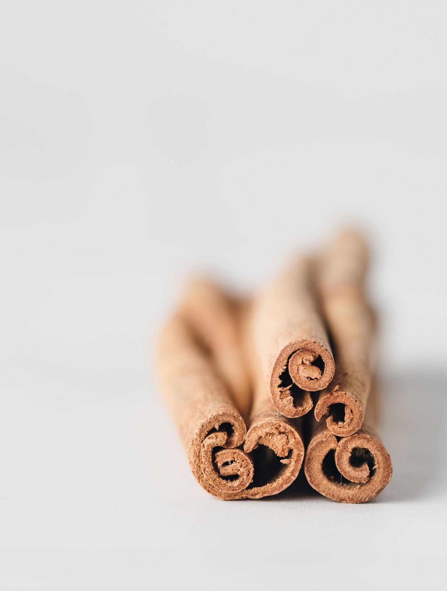 tops of horizontal cinnamon sticks on a white background