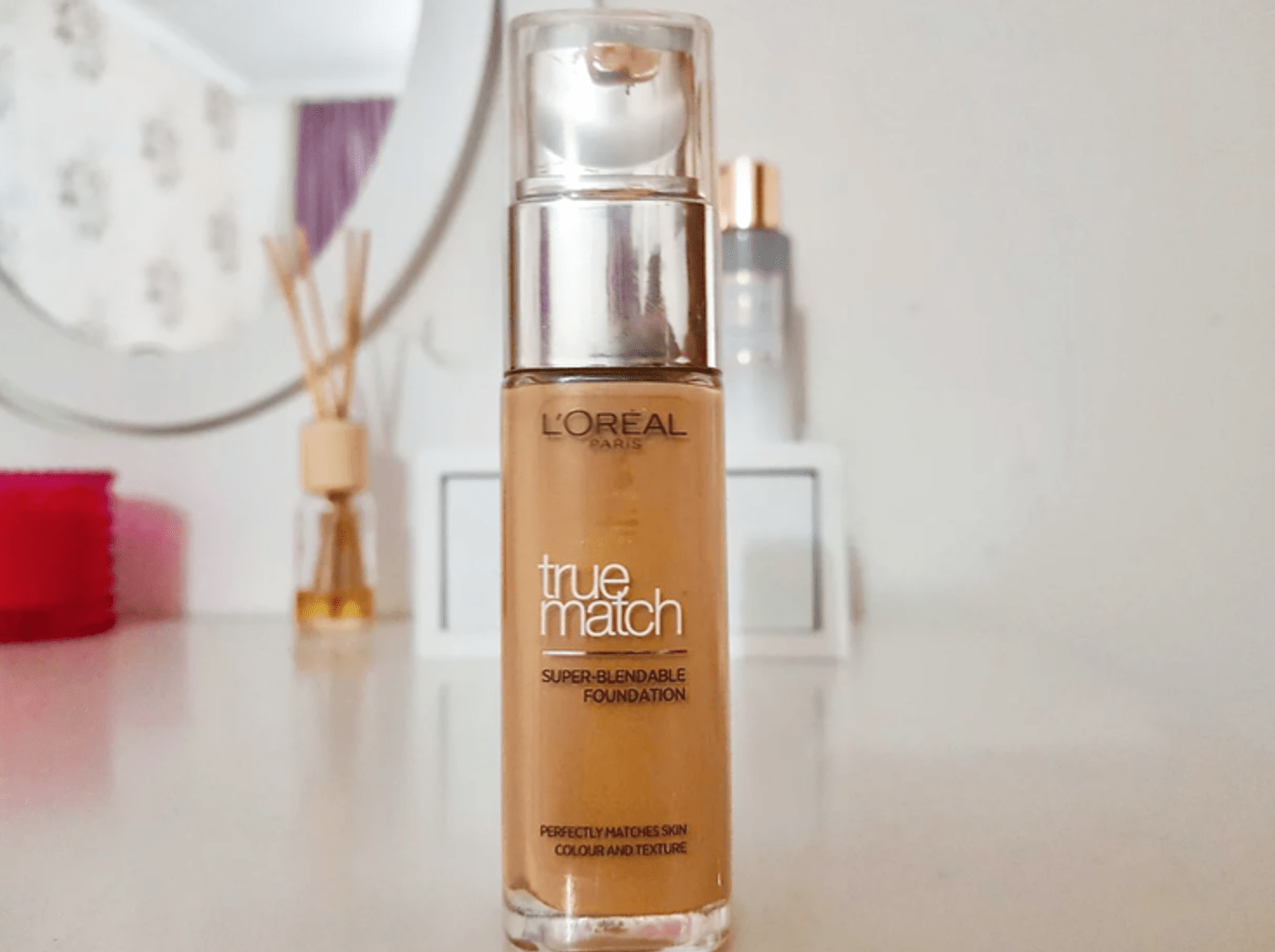 loreal truematch dark skin foundation, on a white glossy table top with a reed diffuser and mirror behind it.