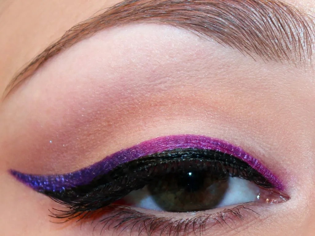 no eyeshadow: a close up of a woman's eye, with both black eyeliner and bright purple.