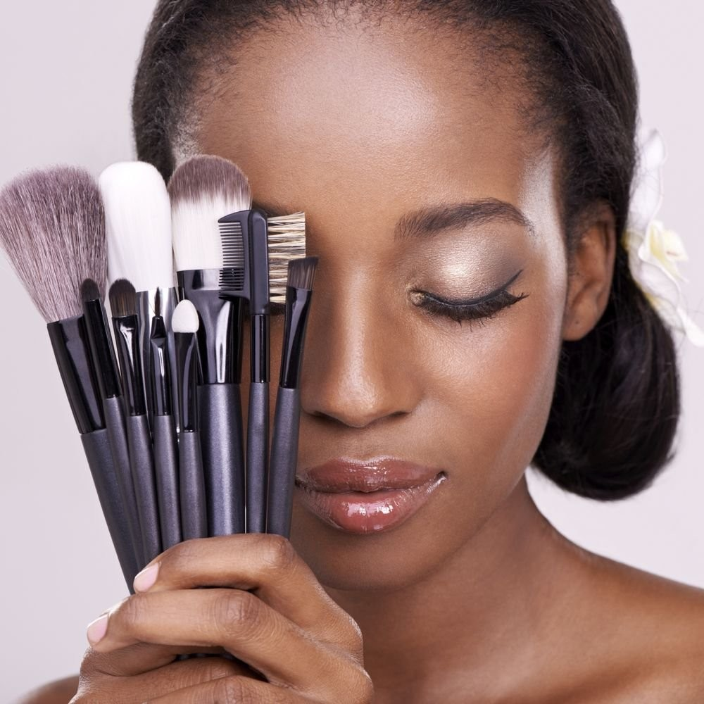 woman holding makeup brushes , like a fan, covering one of her eyes.