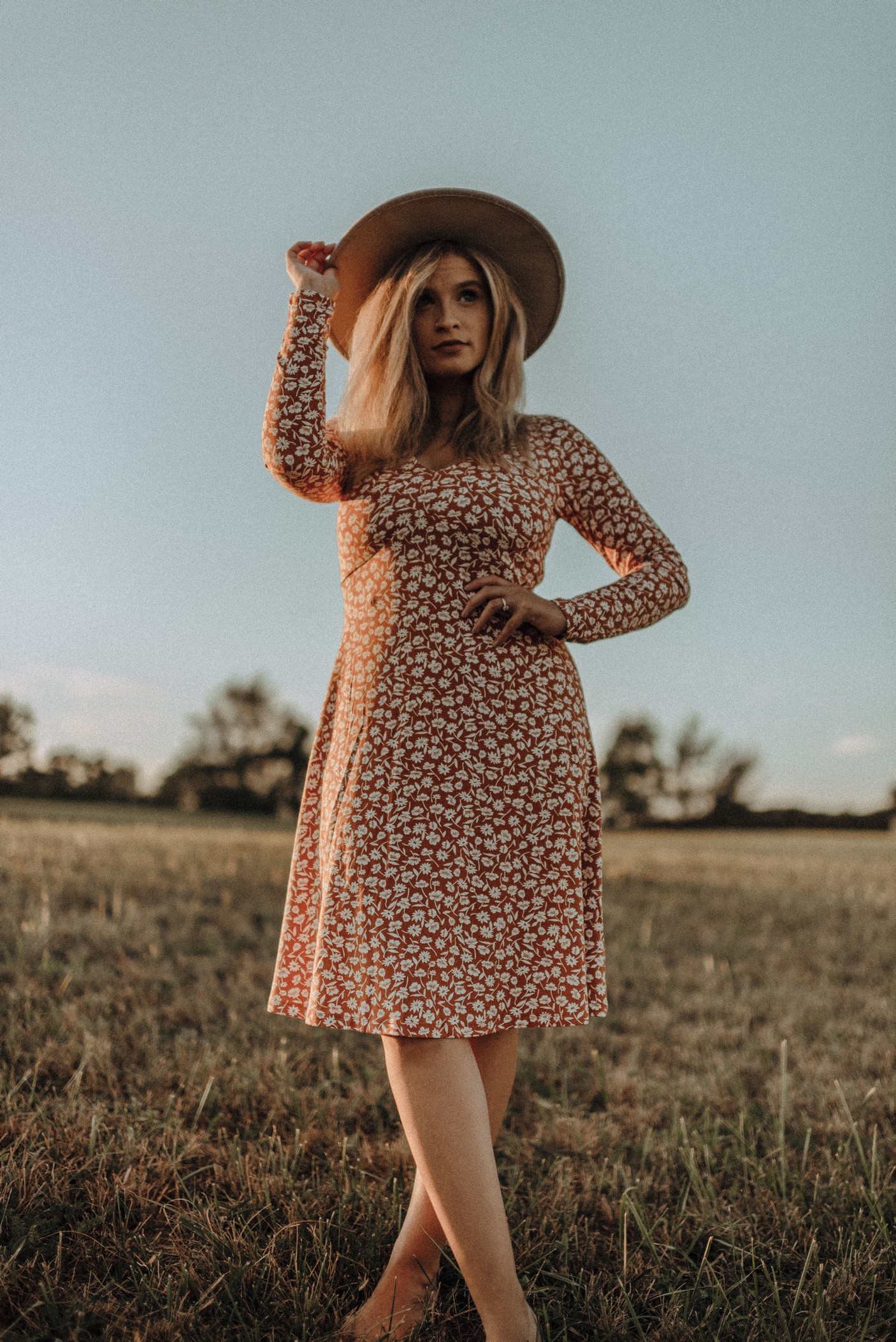 a woman standing in a field, during a heatwave, wearing a long dress and hat.