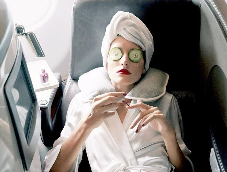 woman lying on plane seat whilst wearing a face mask, in a robe, and has cucumber slices on her eyes.