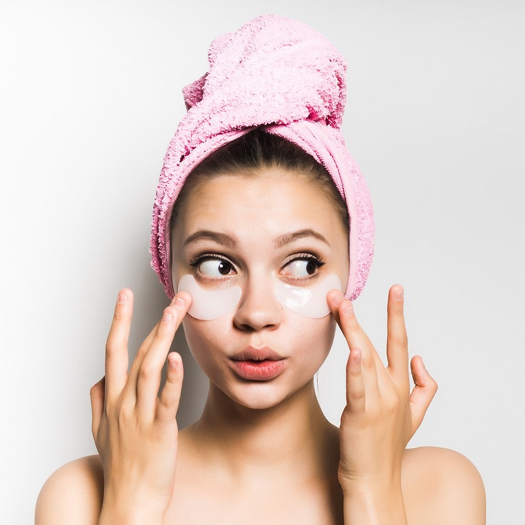 woman pouting whilst rubbing cream into her under eye, wearing a pink towel to hold up her hair.