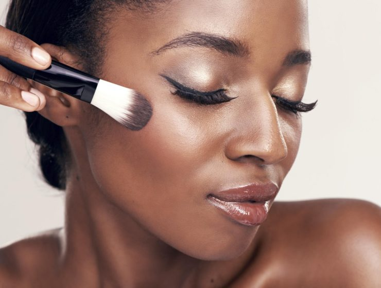 a woman, with her eyes closed, putting makeup on with a foundation brush.