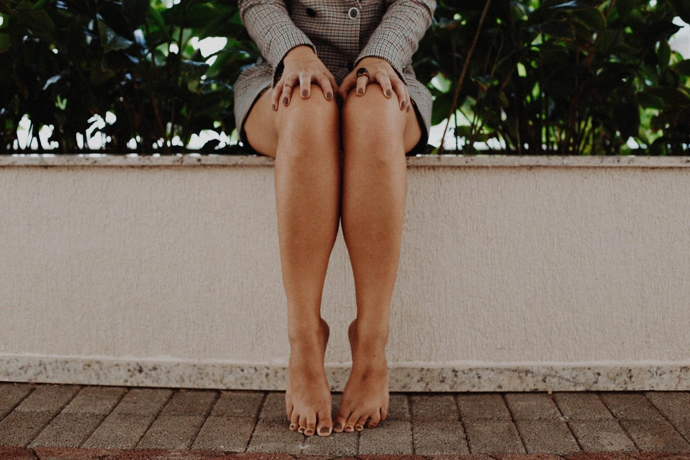 woman sitting on a wall with bare legs and painted toes