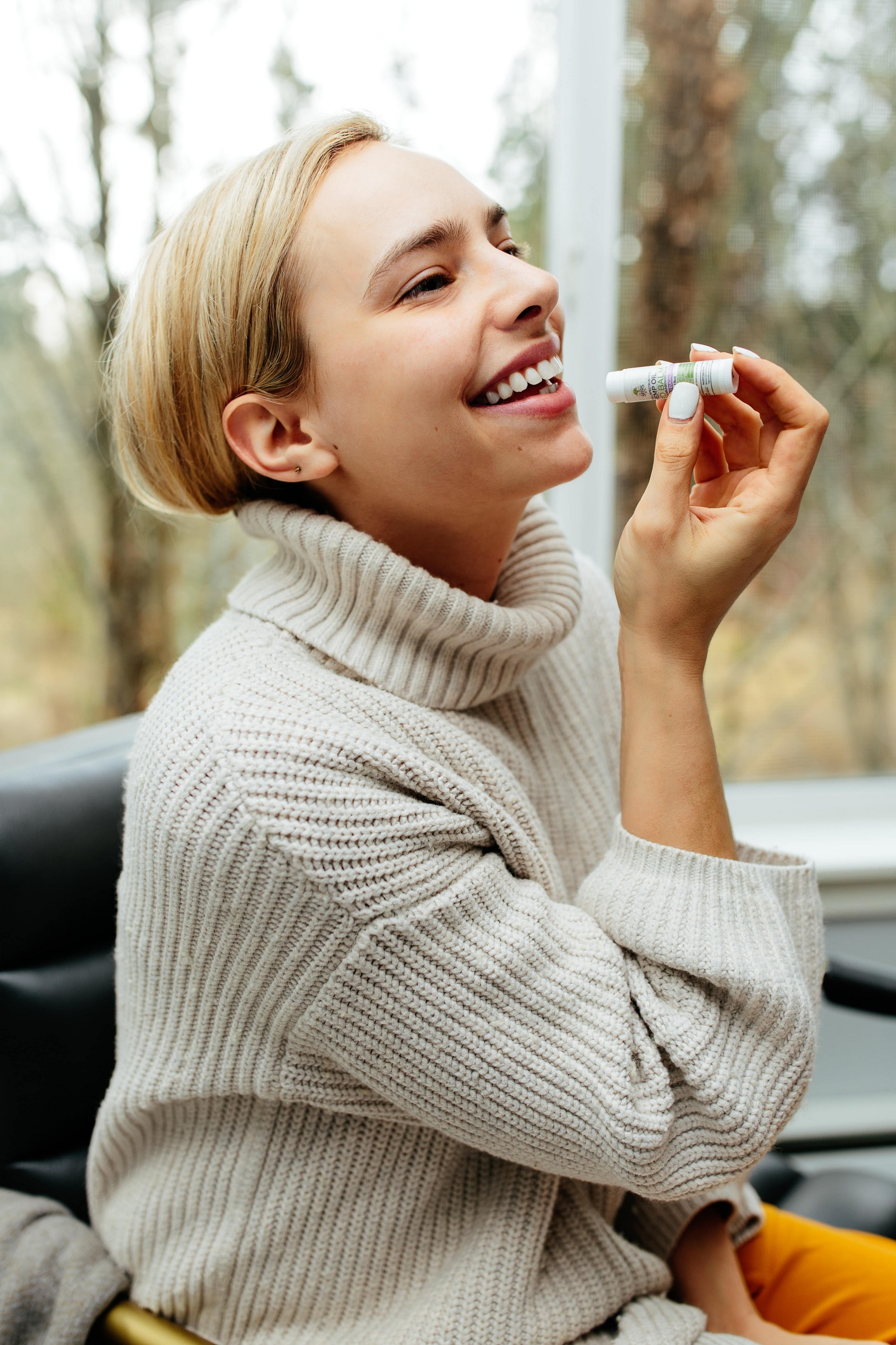 woman smiling whilst putting on lip balm whilst wearing wooly jumper, lip balm is essential at preventing dry lips.