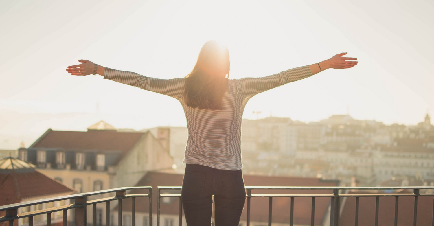 woman standing at a balcony, facing outwards, with her arms spread looking towards the sun.