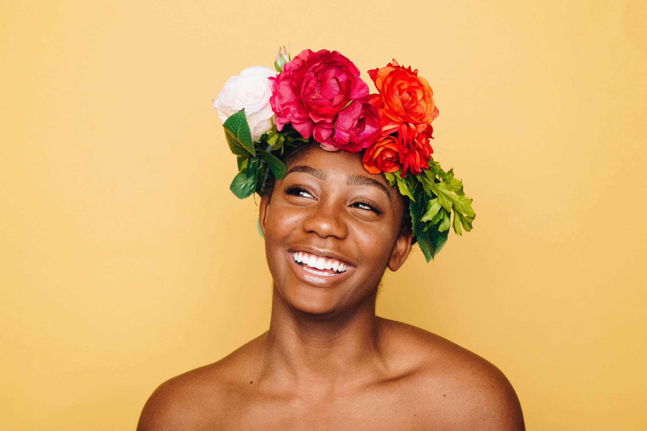 woman with flowers around her head, like a crown, smiling towards the camera with an orange background