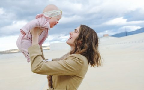 woman holding a baby up high, as they both smile at each other, with a beach in the background.