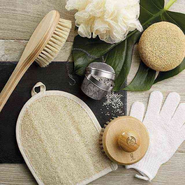 a collection of body shop products, including a body brush, body scrub glove and body scrunchie. on a wooden background with black mat and a bamboo leaf.