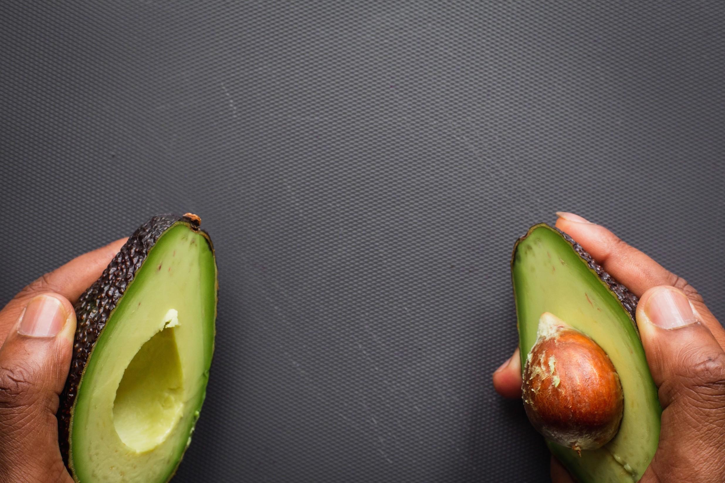 a mans' hands holding a split avocado.