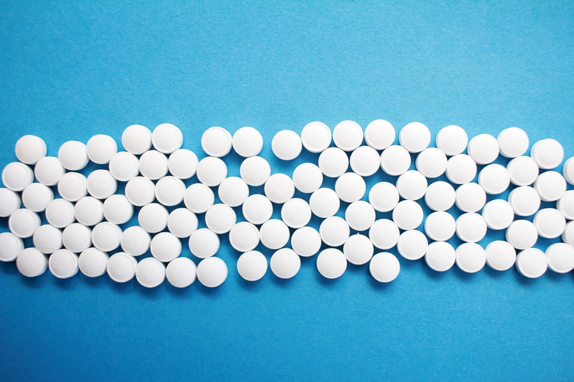 array of white vitamin pills on a blue background.