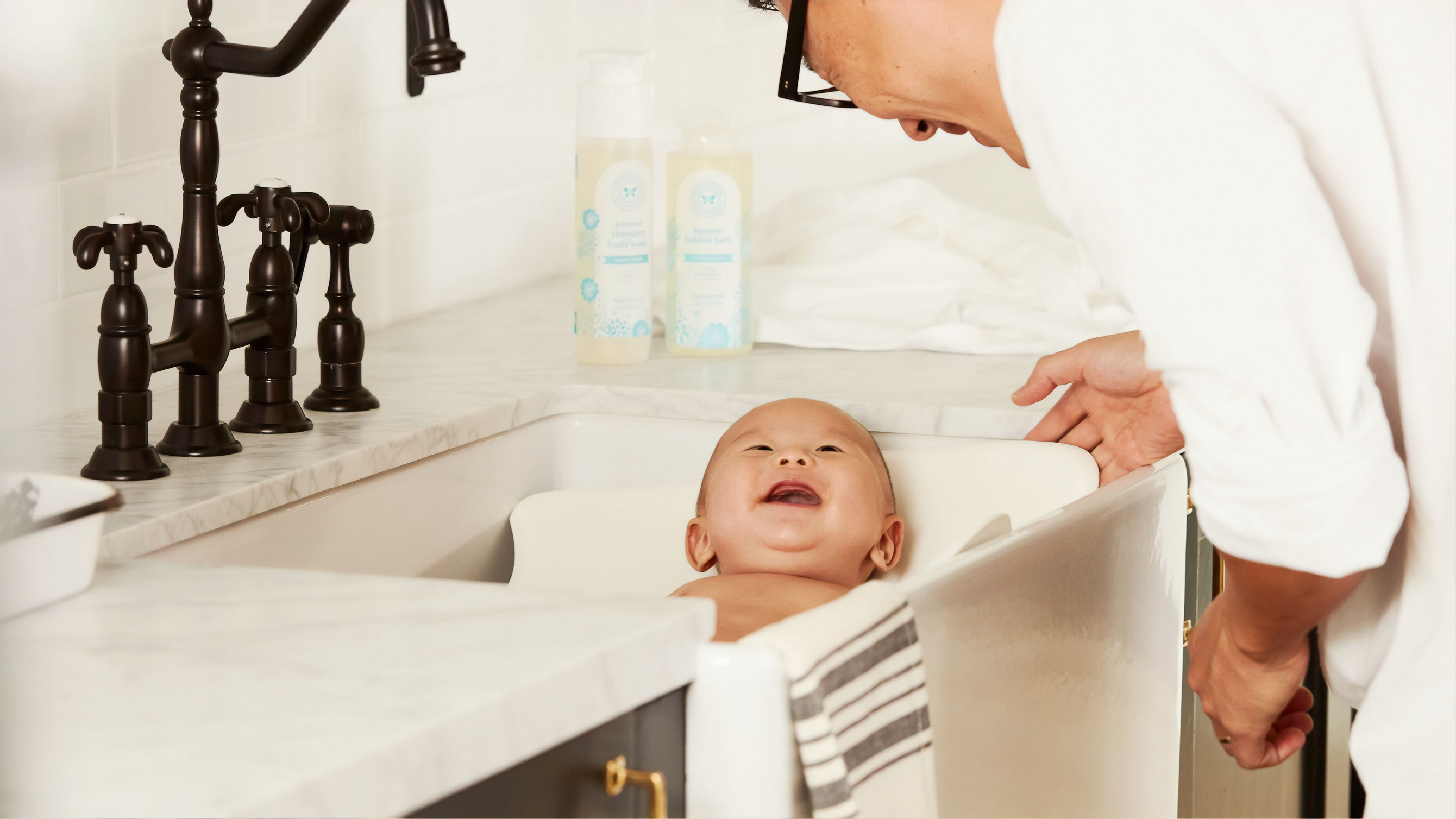 baby lying in sink, looking upwards to a parent and laughing.