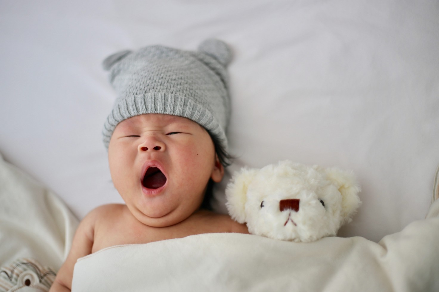 baby lying, yawning, next to a teddy bear whilst under a blanket and wearing a grey hat.