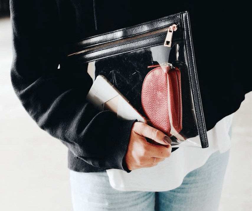 Lady carrying packed clear bag with cosmetics inside