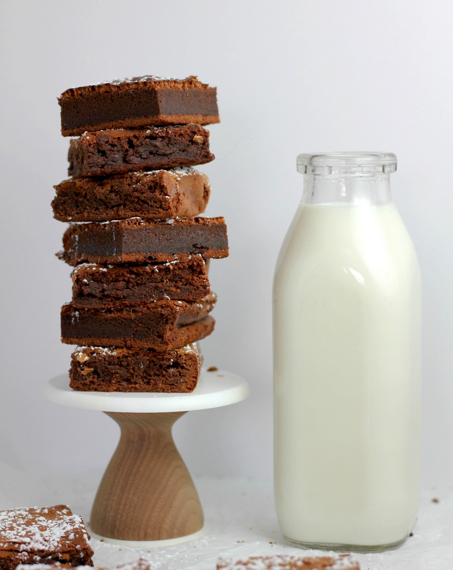 dairy in your diet: a glass bottle of milk sat beside a short tower of chocolate brownies.