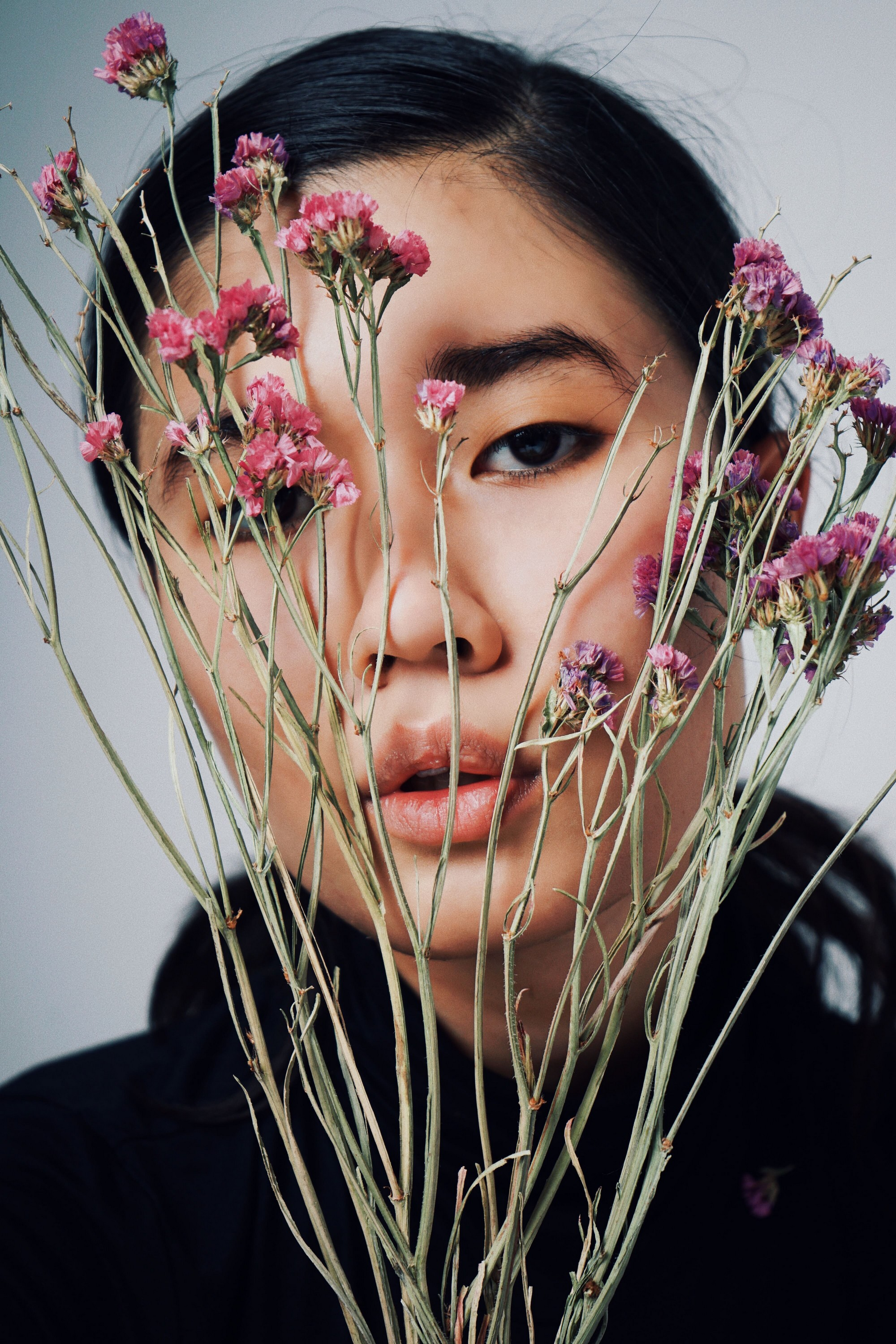 close up of womans' face posing whilst holding flowers in front of her face.