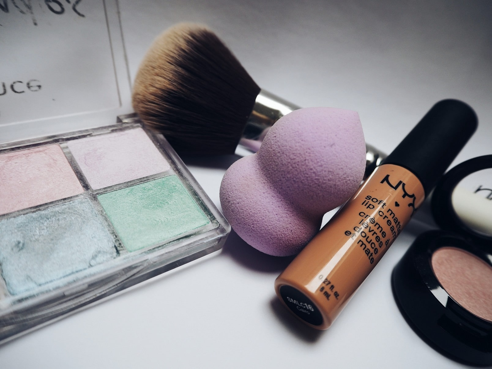 cosmetics, various eyeshadow colours, a beauty blender and brush.