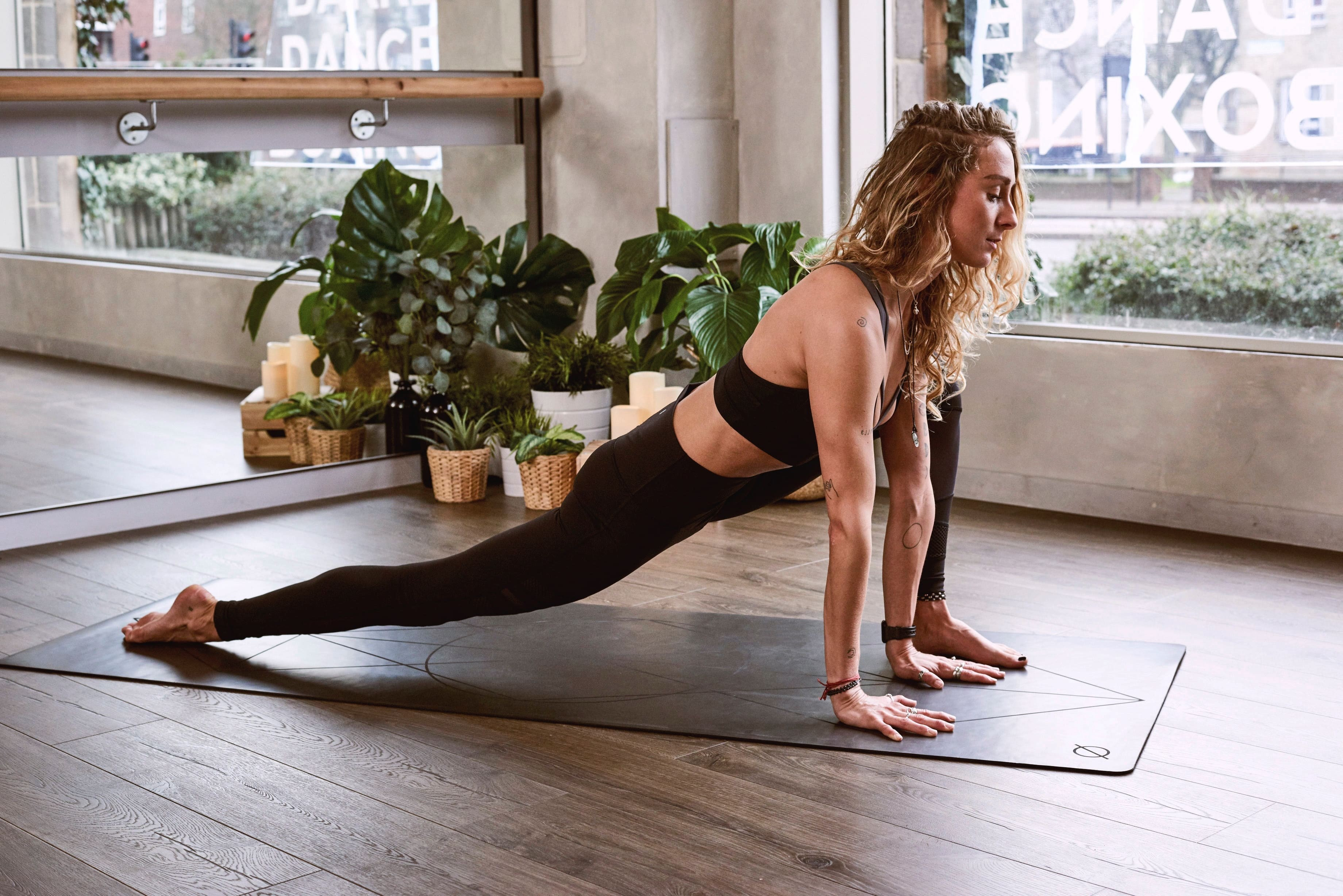 woman doing yoga in a relaxed studio, with a window and mirror in background.