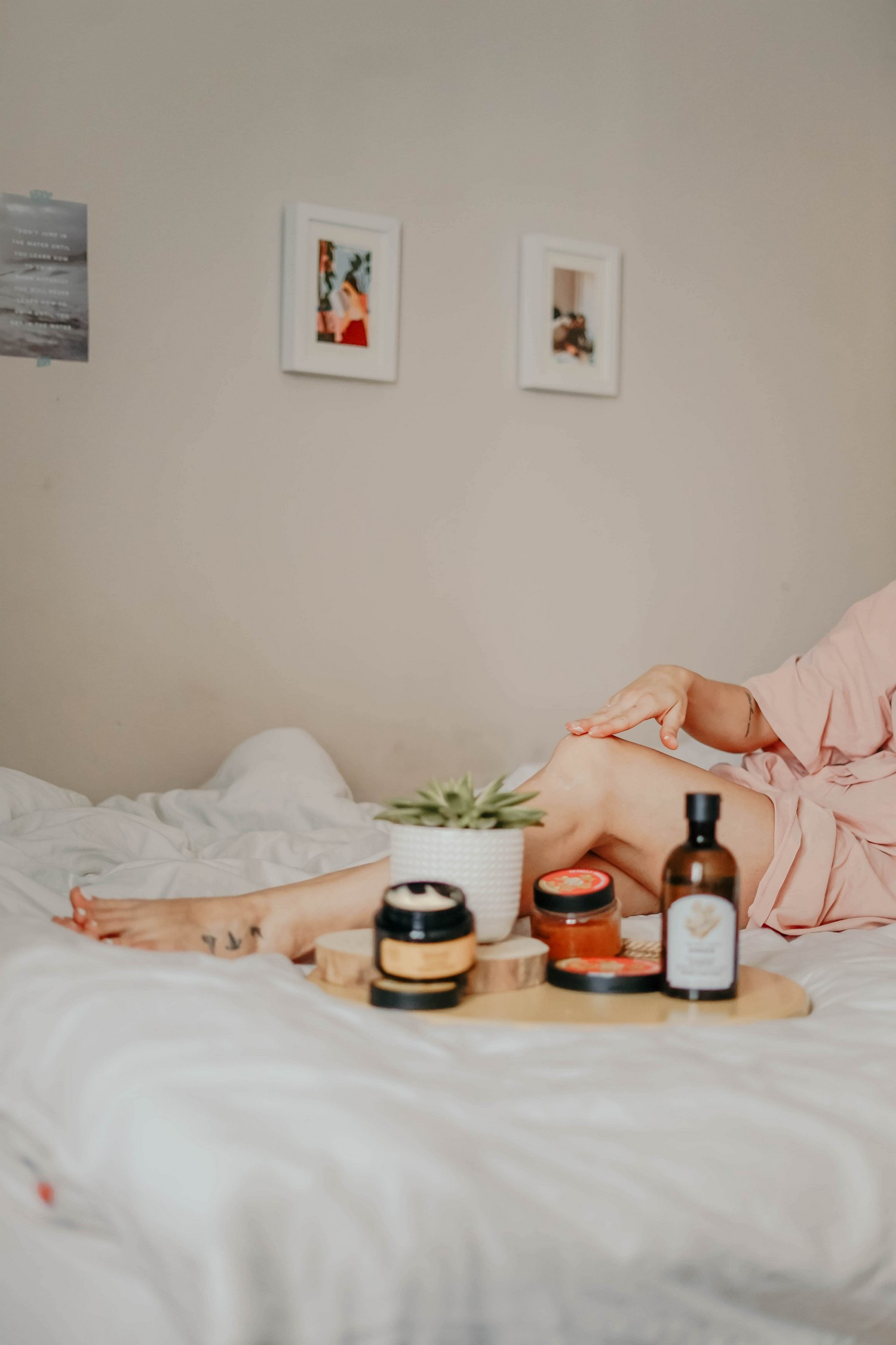 woman pictured on a bed, with white bedding, and an array of beauty products.
