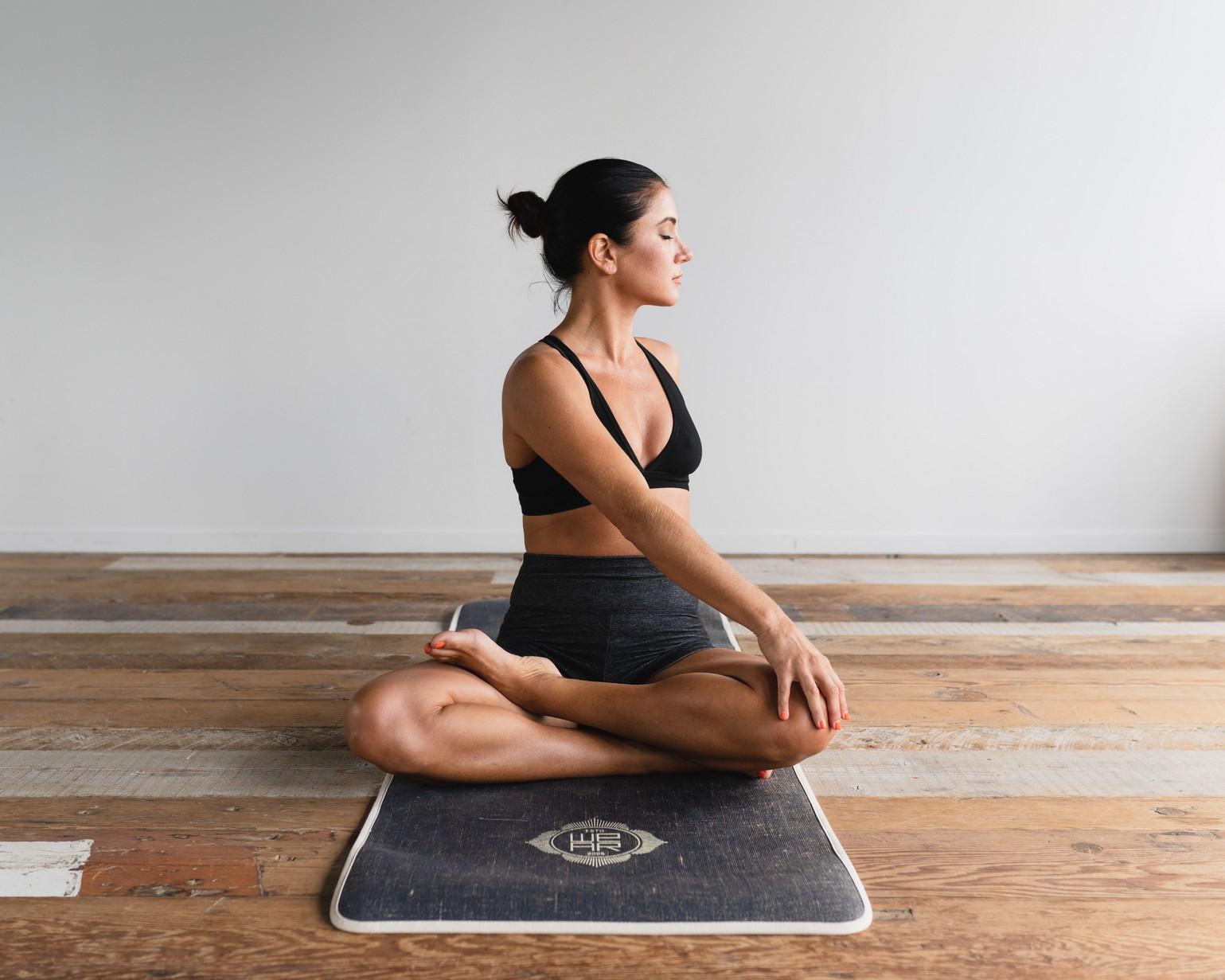 woman sat on yoga mat posed.