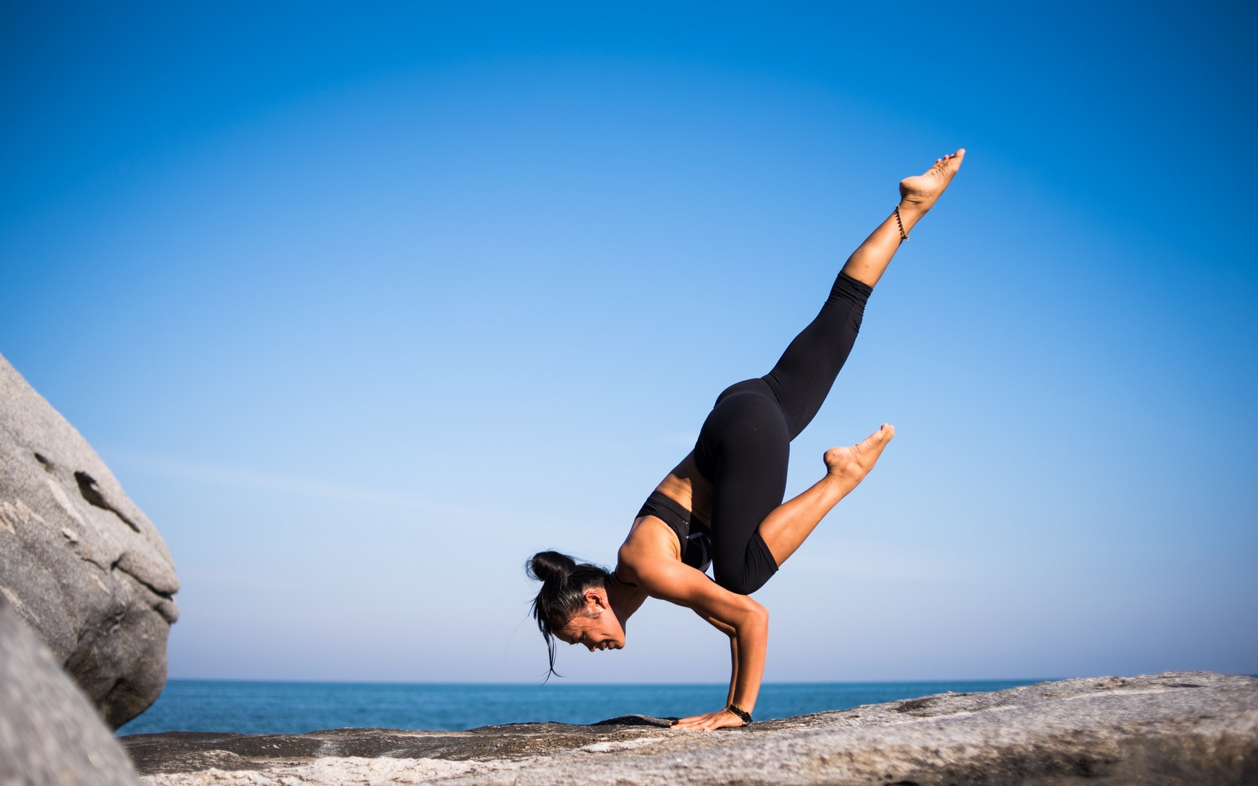 woman in yoga pose, on a large rock, with a bright blue sky and sea behind her.