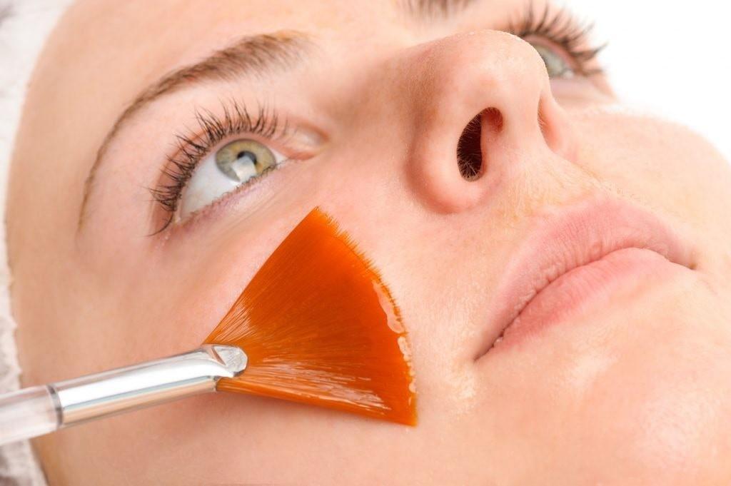 woman having Retinol applied to face with an orange makeup brush.