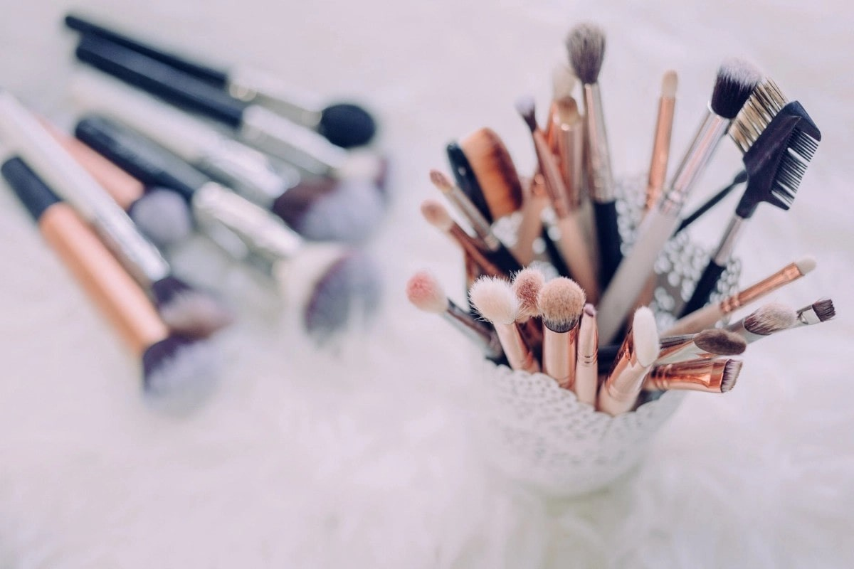 makeup brushes in white floral-cut-pattern cup.